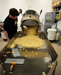 Ben Fox pours a fresh batch of popcorn onto a table where small and un-popped kernels can be separated from the good stuff.