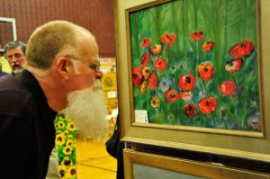 Not all the art was on paper or canvas. Jim daly, of Ardmore, with his national freestyle championship beard, checks out the art  at Chadds Ford Elementary School.
