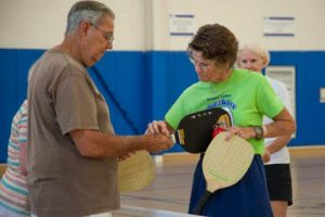 Betsey Cheesman, right, reviews the finer points of gripping a pickleball paddle.