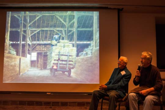 "Father and son Karl Kuerner Jr., left, and Karl J. Kuerner III, provide commentary during a slide show presentation regarding the Kuerner Farm, Andy Wyeth and art. The younger Kuerner said his painting of his father entitled ""Unloading Straw"" is ""the ultimate portrait of my father."""