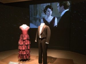 The attire of Lady Mary and Matthew Crowley is set in front of a screen that plays their marriage proposal scene.