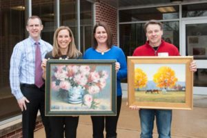 From left are Chadds Ford Elementary School Principal Shawn Dutkiewicz, Art Sale and Show co-chairs Kara Hyman and Meg Niemkiewicz, and featured artist Shawn Faust. Faust is showing Autumn Trio, while Hyman and Niemkiewicz are holding a piece from donating artist Ana Delia McCormack. Not shown is Lisa Albany, the third co-chairman of the event.