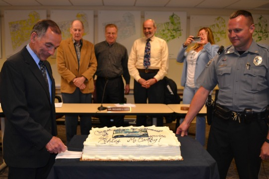 Former Kennett Township Police Chief Albert J. McCarthy (from left) cuts his retirement cake as Supervisors Robert A. Hammaker, Richard L. Leff, Scudder G. Stevens, Township Manager Lisa M. Moore, and acting Police Chief Lydell Nolt look on.