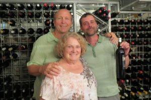 Eric Stauffer (top right) shows off a bottle of [Ee'z], a family collaboration, with his parents, Eric and Lee Miller, in the wine cellar of their West Chester home.