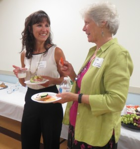 Kate Uhler, discusses Family Promise with volunteer Mary Boeni during a reception following the signing ceremony.