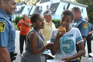 Kennett Square Police Officer Jonhathan Ortiz  (from left) enjoys watching Aalana Vasquez and Johnnette Boddy devour their pizza.