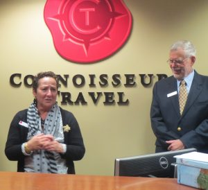 Cathy Hagle (left) addresses the crowd at the grand opening of Connoisseur Travel in Kennett Square, as her husband, George Hagle, who co-founded the business with her, looks on.