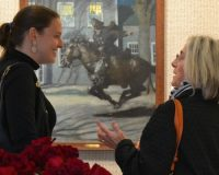 Against the backdrop of one of her great-grandfather's paintings, Victoria Wyeth (left) chats with a guest at the Chester County Art Association, where an exhibit of rarely viewed N.C. Wyeth works is on display.