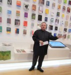 Bruce Mao in front of the wall of books he designed