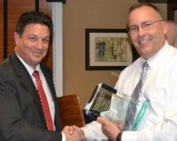 Jose Reyes (left), board president of the Chester County Crime Victims' Center, congratulates West Goshen Det. David Maurer, one of the co-recipients of the 2015 John J. Crane award for victim advocacy.