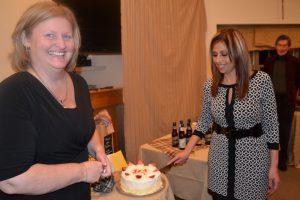 CFHS Board President Kendal Reynolds (left) assists Nadia Barakat her final duty: cutting cake.