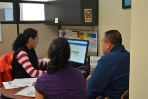 ristina Gonzalez, LCH Front-End Supervisor and Certified Application Counselor, helps a family with health insurance enrollment application. Photo courtesy of La Comunidad Hispana