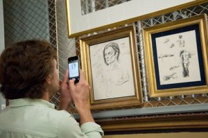 Actor William Connell, who portrays Jamie Wyeth, takes photos of some of Wyeth's sketches of Rudolf Nureyev.