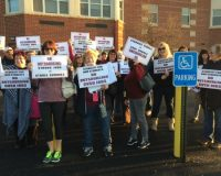 Members of the Garnet Valley Educational Support Professionals Association and their supporters assemble with placards outlining their position on outsourcing before Tuesday night's school board meeting.