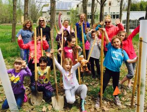 Members of Brownie Troop work on planting trees in the streamside forest buffer near the education wing of the Stroud Water Research Center.