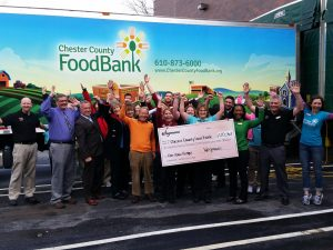 Robert McNeil, wearing an orange shirt, joins employees from Wegmans and the Food Bank after the supermarket made one of several large donations to the agency this past spring.