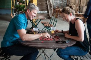 David Fierabend and Molly Lux, of the Groundswell Design Group, play some checkers during the opening of The Creamery. Groundswell did the design for the beer garden.