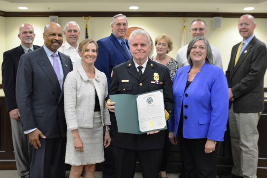 Accompanied by County Commissioners Terence Farrell (from left, front row), Michelle Kichline and Kathi Cozzone (right), Chaplain Jerry Schwartz holds a proclamation for National Post-Traumatic Stress Disorder Awareness Month. Behind them are members of the county's Critical Incident Stress Management Team.