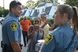 As Aalana Vasquez enjoys pizza, Kennett Square Police Officers Johnathan Ortiz (left) and Sarah London converse during the 2015 National Night Out. To Ortiz's right is Borough Councilman Geoffrey R. Bosley.