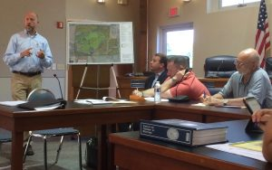 Andrew J. Semon (left), division president for Toll Brothers, discusses plans for Crebilly Farm as Gregg I. Edelman, a Toll Brothers attorney, and Westtown Township Supervisors Thomas F. Haws and Mike T. Di Domenico listen.