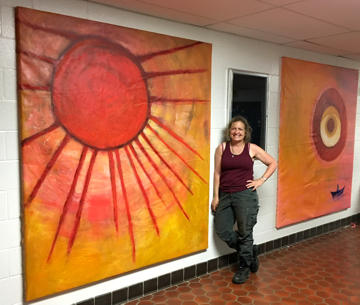 Lele Galer stands in front of Sun Mural at Patton Middle School