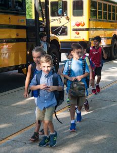 Students get off the buses and walk to class for the first day of the new school year.