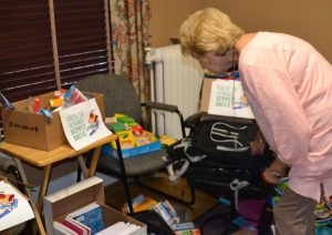 Peggy Gusz, executive director of the Crime Victims Center, surveys the school supplies destined for child crime victims.