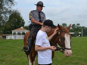 Bryce Rubin, 18, of Lincoln University, makes a new friend, who's ridden by Cpl. Michael Funk