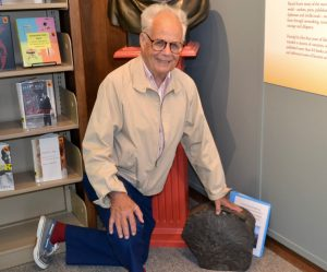 Tom Swett, the Kennett Library board president, shows off an 1844 rock that is part of a tribute to Bayard Taylor.