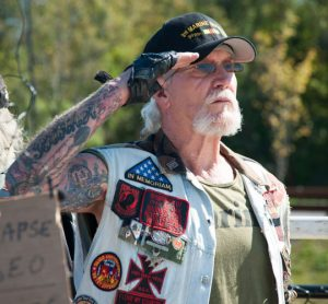 """Marine veteran Chuck """"Graves"""" Roth salutes the colors during a ceremony he says was long overdue."""