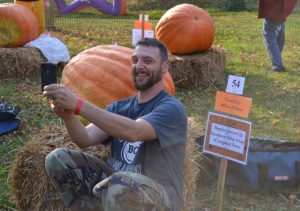 Bill DeHaven takes a selfie with his pumpkin before he begins to dissect it.