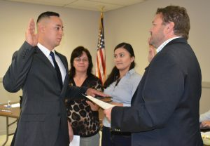 Miguel Juarez (left) recites the oath from Mayor Matt Fetick (right) to become a part-time police officer.