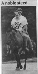 """Mindy Rhodes is shown riding """"Sir Noble"""" bareback on South New Street with a high school friend in a newspaper clipping."""