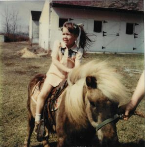A family photo from Mindy Worth Rhodes' 5th birthday party attests to her lifelong passion for horseback riding.