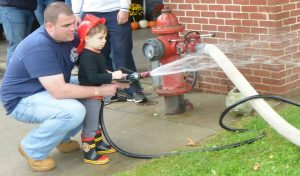 Longwood Fire Company Chief A. J. MaCarthy gives instructions to his son Jeremy during the open house celebration.