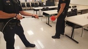 Two deputy sheriffs practice the operation of a control pole, using a balloon to gauge the correct application of pressure.