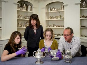 Senior Objects Conservator Bruno Pouliot (from right) works on silver objects with Kaitlin Andrews, a conservation technician; Curator of Decorative Arts Ann Wagner, and Maggie Bearden, a conservation technician during the first phase of the grant-funded project.