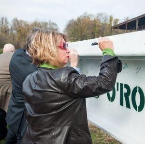 Former Chadds Ford Supervisor Debora Love signs her name to the beam used to top off the building. Love was one of the supervisors who approved an office building on that lot.
