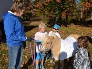 Tracey Norcini of the Parkesburg chapter of Kacie's Cause explains the rules for being able to sign the shirt sported by the chapter's mascot: Abe, a miniature horse.