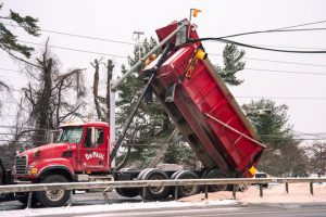 A sand truck hits overheard power lines and traffic signal.